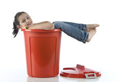 Girl playing with red bin Stock Images