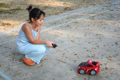 Girl playing remote control car. Girl playing red remote control car at the children playground Royalty Free Stock Images