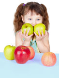 Girl playing with ripe apples sitting at table Royalty Free Stock Image