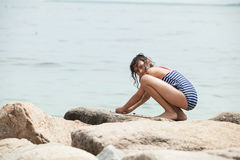 Girl playing on a rocky beach Stock Image