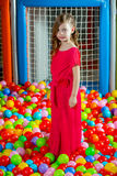 Girl in the playing room with many little colored balls Stock Photos