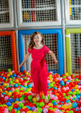 Girl in the playing room with many little colored balls Stock Images