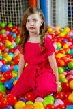 Girl in the playing room with many little colored balls Stock Image