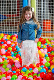 Girl in the playing room with many little colored balls Royalty Free Stock Image