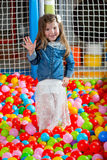 Girl in the playing room with many little colored balls Royalty Free Stock Photography