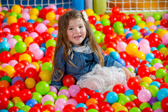 Girl in the playing room with many little colored balls Stock Photography