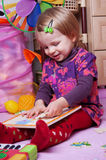 Girl in playing room with puzzle Royalty Free Stock Photography