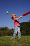 Girl playing rounders. A young girl batting a ball, playing rounders (softball Stock Photography
