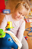 Girl playing with rubber donkey toy Royalty Free Stock Image