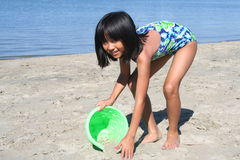 Girl Playing in Sand. Girl shoveling sand into a bucket at the beach Royalty Free Stock Photos