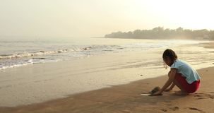 Girl playing sand alone on beach. Video footage of a little girl with casual clothes, playing sand alone on the tropical beach in the morning. Shot in 4k stock footage
