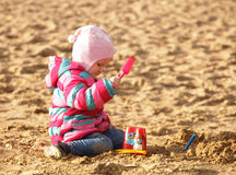 Girl playing with sand at the autumn beach Stock Photo