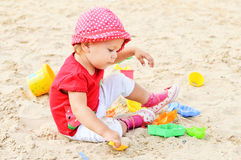 Girl playing in sand Stock Image