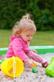 Girl playing in a sand box. Little girl playing in a sand box stock images