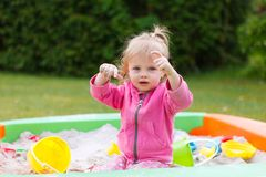 Girl playing in a sand box. Little girl playing in a sand box stock photos