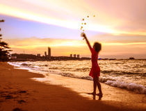 Girl playing sand cast on the beach and sunset time Stock Photo