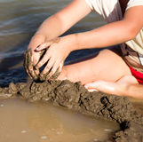 Girl playing in the sand on the lake royalty free stock photos