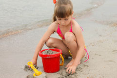 Girl playing with sand on the sea shore Royalty Free Stock Photos