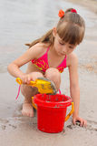 Girl playing with sand on the sea shore.  Royalty Free Stock Images