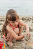 Girl playing with sand on the sea shore.  Royalty Free Stock Photography