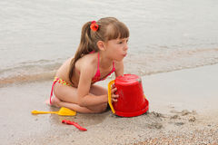 Girl playing with sand on the sea shore.  Stock Photos