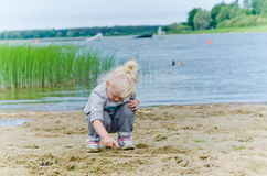 Girl playing in the sand on shore of Lake Stock Photos