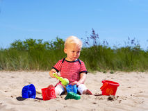Girl playing in the sand with shovel and bucket. One year old girl lad playing in the sand with shovel and bucketwith shovel and bucket Stock Photo