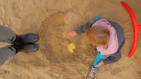 The Girl Is Playing In The Sandbox. The Sandbox, A Little Blonde Sculpts Figurines From Sand. The Girl Is Playing In The Sandbox. The Sandbox, A Little Blonde stock footage