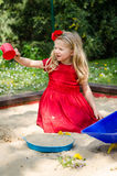 Girl playing in sandpit Stock Images