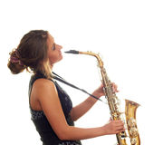 Girl playing the saxophone. Girl with a saxophone in a black dress isolated on white background Stock Image