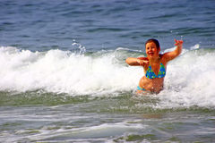 Girl playing in sea. Young girl playing in waves and surf in sea Stock Photos