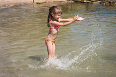 Girl playing on the sea, sprinkles water Royalty Free Stock Image
