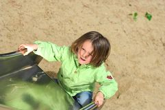 Girl playing on slide Stock Photos