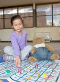 Girl Playing Snakes and Ladders with Teddy Bear. A young girl of Asian descent smiles as she rolls the die during a game of Snakes and Ladders with her teddy royalty free stock photos