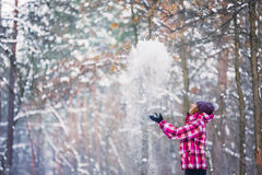 Girl playing with snow in park. Winter time stock image
