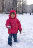 Girl playing snowballs. The little girl in a red jacket playing snowballs Stock Photography