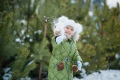 Girl playing snowballs. Funny little girl having fun in winter park. making snowballs happy child girl. winter girl throwing stock photos