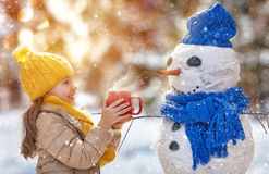 Girl playing with a snowman Royalty Free Stock Images