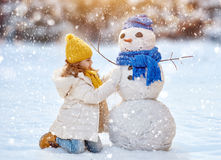 Girl playing with a snowman. Happy child girl plaing with a snowman on a snowy winter walk Royalty Free Stock Image