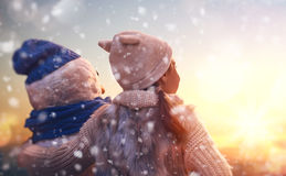 Girl playing with a snowman. Happy child girl playing with a snowman on snowy winter walk in nature. Frost winter season Stock Photography