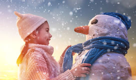 Girl playing with a snowman. Happy child girl playing with a snowman on snowy winter walk in nature. Frost winter season Stock Images