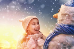 Girl playing with a snowman Royalty Free Stock Image