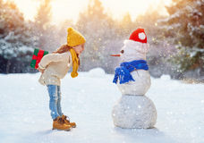 Girl playing with a snowman Royalty Free Stock Photo