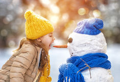Girl playing with a snowman Royalty Free Stock Photography
