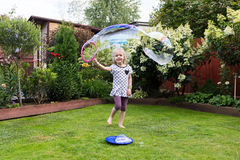 Girl playing with soap bubbles in beautiful garden Stock Photo