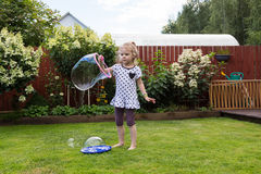 Girl playing with soap bubbles in beautiful garden Stock Images