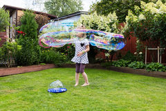 Girl playing with soap bubbles in beautiful garden Stock Photos