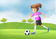 A girl playing soccer at the field Royalty Free Stock Photos