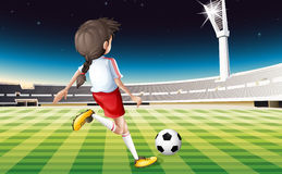 A girl playing soccer at the field Royalty Free Stock Photography