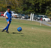 Girl playing soccer with focus. African American girl playing soccer, with focus on the ball stock photo